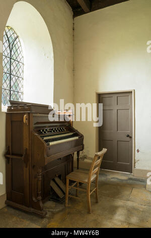 Interior of quaint historic St Martin's Church with small traditional wooden organ in corner -  Allerton Mauleverer, North Yorkshire, England, UK. - Stock Photo