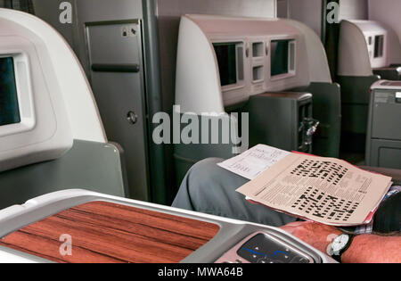 Business Class seats LATAM airlines Dreamliner 787 with man doing Guardian Easter Crossword, flying from Easter Island to Santiago - Stock Photo