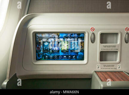 Business Class seats LATAM airlines Dreamliner 787 flying from Easter Island to Santiago, with video console showing in flight entertainment movies - Stock Photo