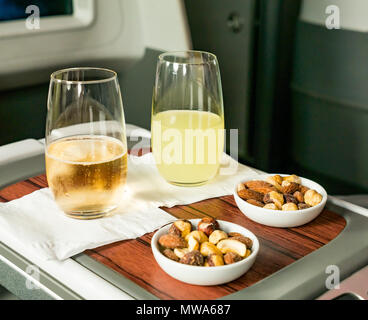 Business Class seats LATAM airlines Dreamliner 787 flying from Easter Island to Santiago; pisco sour and sparkling wine welcome drinks with mixed nuts - Stock Photo