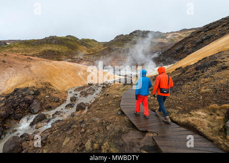 Two hikers, Steaming Soil, Seltún Geothermal Area, Krýsuvík Volcano System, Reykjanesfólkvangur National reserve, Iceland - Stock Photo