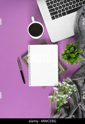 Home work space with notebook, laptop and coffee on pastel violet background. Home office flat lay top view. - Stock Photo