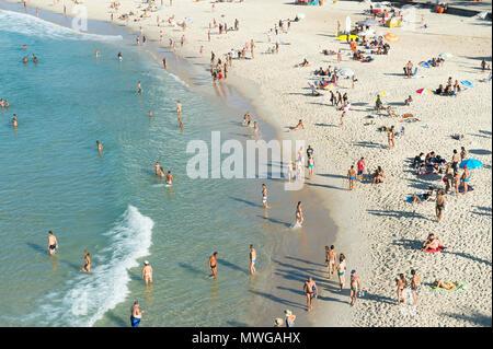 RIO DE JANEIRO, BRAZIL - FEBRUARY 02, 2014: Beachgoers relax on the shore of Ipanema Beach. - Stock Photo