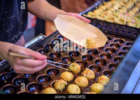 Takoyaki being prepared at a foodstall in Osaka, Japan. - Stock Photo
