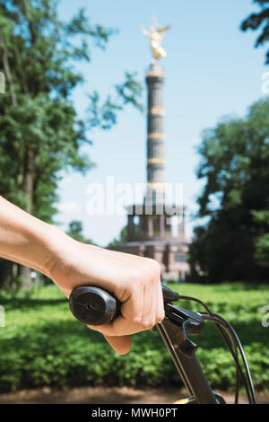 closeup of a young caucasian man riding a bike by the Tiergarten park, in Berlin, Germany, with the popular Victory Column in the background - Stock Photo