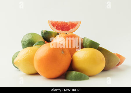 Grapefruit slice on heap of citrus fruits isolated on white background - Stock Photo