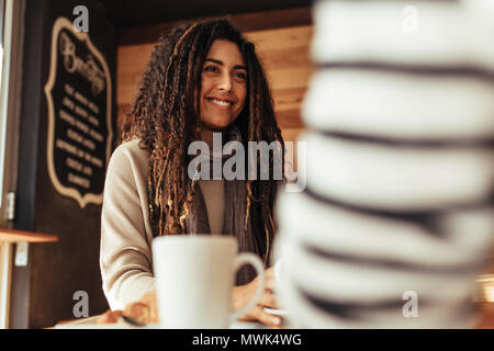 Smiling woman sitting in a restaurant talking to her friend. Friends sitting at a cafe with coffee on the table. - Stock Photo