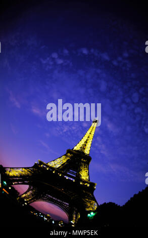 Eiffel Tower, looking northwest down Champ de Mars and up at dusk, depicting lights on a with little fluffy clouds and twilight glow, Paris, France - Stock Photo