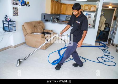 Miami Beach Florida carpet cleaning cleaner Hispanic man service home house vacuum vacuuming machine uniform job working - Stock Photo