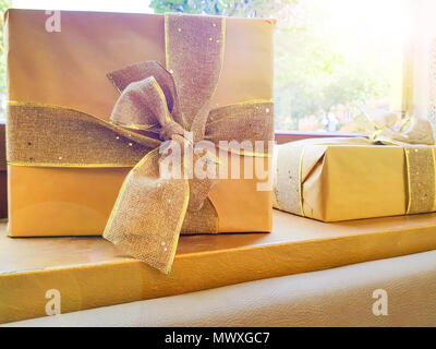 Large brown gift box on the table located by the clear window, Gift box or present wrapped with kraft paper and a large ribbon. - Stock Photo