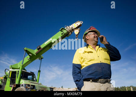 A man talking on a radio with mobile crane in the background. - Stock Photo