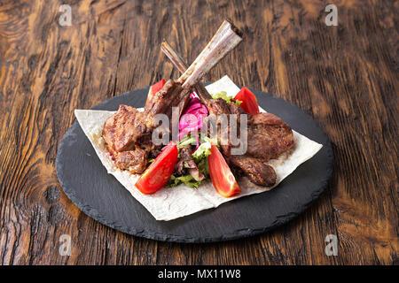 ribeye steak on the bone, tomahawk, served with tomatoes and iceberg lettuce on pita on slate board. - Stock Photo