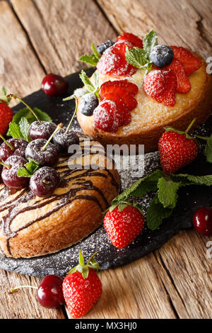 Freshly baked two cakes with chocolate, mint, strawberry, cherry and blueberry close-up on the table. vertical - Stock Photo