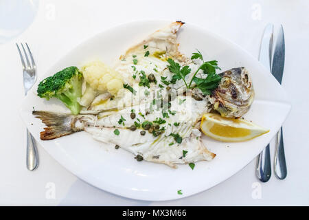 Fine dining: a main course of grilled sea bream (dorade) served on a white plate with a garnish of capers, broccoli and cauliflower and slice of lemon - Stock Photo