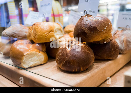 Closeup of fresh brown whole wheat dark sourdough baked bread loaves rolls in bakery with many buns, challah - Stock Photo