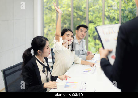 Asian woman is raising her hands has question while businessman presentation about business sale report at the meeting room - Stock Photo