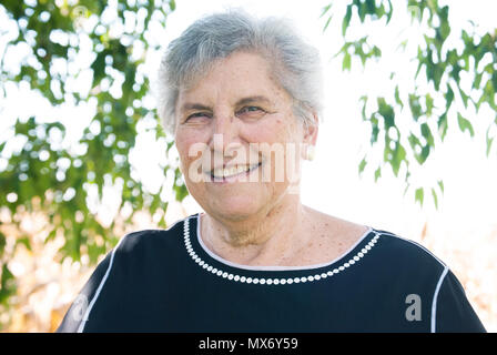Old woman smiling with trees in background - Stock Photo