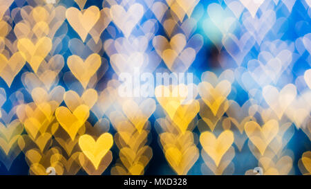 beautiful bokeh made of warm orange blurred lights in the form of hearts on blue background, special photo technique - Stock Photo