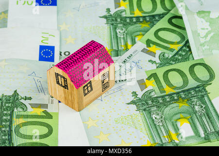 one miniature wooden house laying on one hundred euro banknotes - Stock Photo