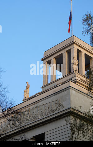 Berlin, Germany - April 14, 2018: Top of Russian Federation Embassy building with flag, statues and USSR coat of arms - Stock Photo