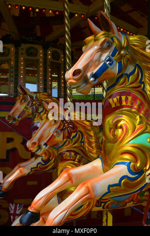 close up of horses on a merry-go-round at the annual Sherborne Castle Country Fair, Sherborne, Dorset, England - Stock Photo