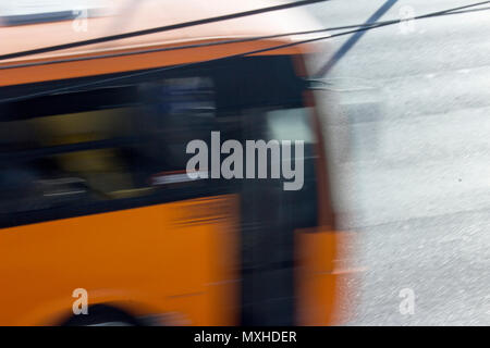 An orange public bus transits in an avenue of Monterrey, Nuevo Leon, Mexico, in the afternoon. - Stock Photo