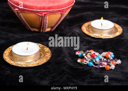 Magical attributes with candles on black background - Stock Photo