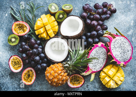 Assortment of exotic tropical fruits, top view. Passionfruit, dragonfruit, mango, pineapple, kiwi, grapes and coconut. Fresh food background. Healthy  - Stock Photo