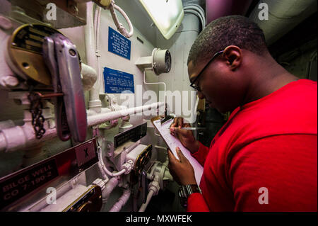 161210-N-IV489-058 ATLANTIC OCEAN (Dec. 10, 2016) Petty Officer 3rd Class Osada Allen, from Brooklyn, New York, inspects a passageway aboard the aircraft carrier USS George Washington (CVN 73). George Washington, homeported in Norfolk, is underway conducting carrier qualifications in the Atlantic Ocean. (U.S. Navy Photo by Seaman Oscar Albert Moreno Jr.) - Stock Photo