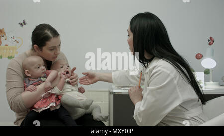 Female pediatrician doctor explain something to mother with newborn baby twins at modern hospital indoors - Stock Photo