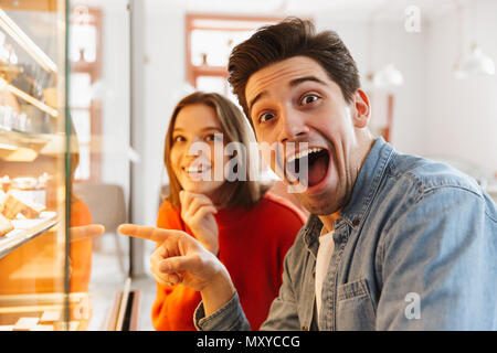 Joyful couple woman and man in casual wear rejoicing while choosing sweets and cakes in cozy bakery - Stock Photo