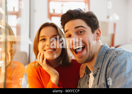 Happy couple woman and man smiling and rejoicing while resting in cozy bakery - Stock Photo