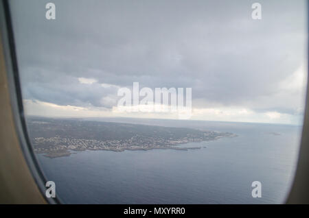 Photograph of the landscape of Menorca from the air with the window of an airplane making a frame. - Stock Photo