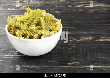 White bowl with raw pasta fusilli on wooden background - Stock Photo