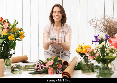 Beautiful florist woman in apron working in flower studio and taking photo with mobile phone of bouquet on table - Stock Photo