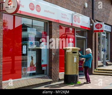 Flint, UK: June 4, 2018: An elderly woman posts some letters in a post box outside Flint Post Office. - Stock Photo