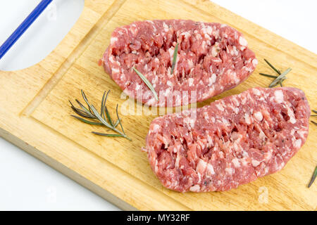 Fresh pork sausages isolated on white background, -raw sausage for cooking on cutting board with rosemary on a white background, top view - Stock Photo