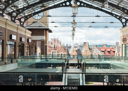 Passage and escalator in empty modern shopping mall at daytime - Stock Photo