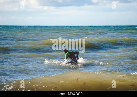 Zelenogradsk, Russia-may 17, 2016: A lone surfer trains on small waves in the Baltic sea - Stock Photo