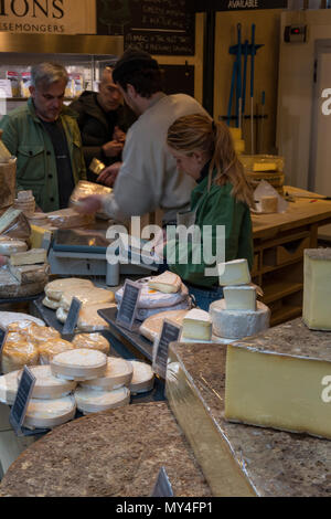 A woman on a cheese counter to market stall at borough market in central london. Serving on a stall selling dairy products on a marketplace stall. - Stock Photo
