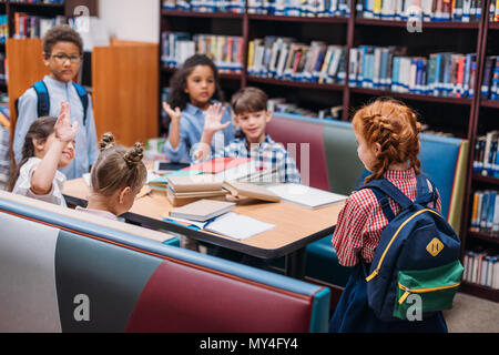 adorable little kids raising hands in library - Stock Photo