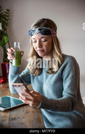 Young woman with vegetable juice looking at smartphone at cafe window seat - Stock Photo