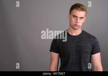 Young handsome man with blond hair wearing gray shirt against gr - Stock Photo