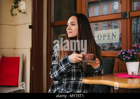 Young beautiful girl drinks coffee or hot chocolate in a street cafe - Stock Photo