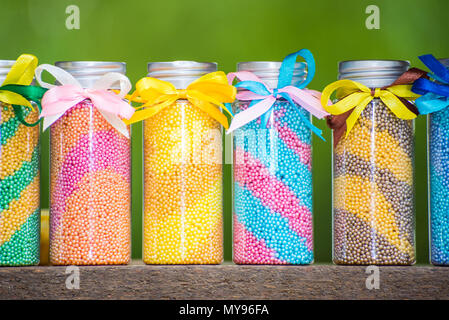 Multicolored bottles with foam for a bath with bows on a green background - Stock Photo