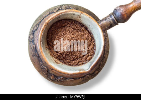 An old coffee maker made in the Middle East. Ground coffee is poured into cold water. Turkish coffee . Isolated photo on a white background. - Stock Photo