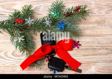 Close-up view of car keys with red bow as present on wooden background. - Stock Photo