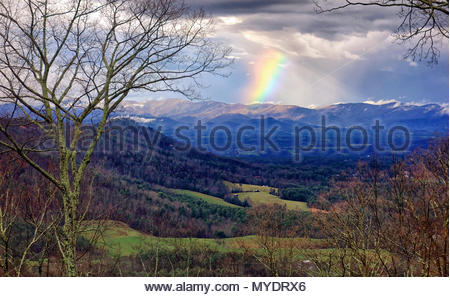 A rainbow shines down on a mountain ridge on a colorful winter morning. - Stock Photo