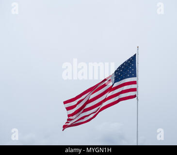 An American flag with stars and stripes blowing in a breeze against cloudy gray sky. - Stock Photo