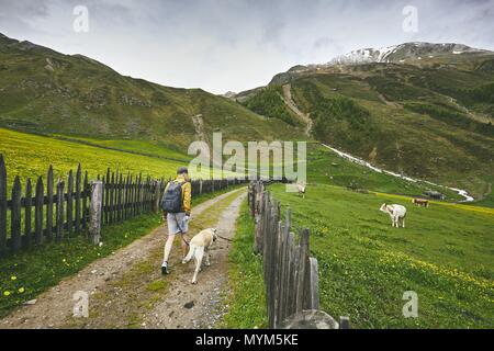 Tourist with dog in countryside. Young man walking with labrador retriever on dirt road. South Tyrol, Italy - Stock Photo